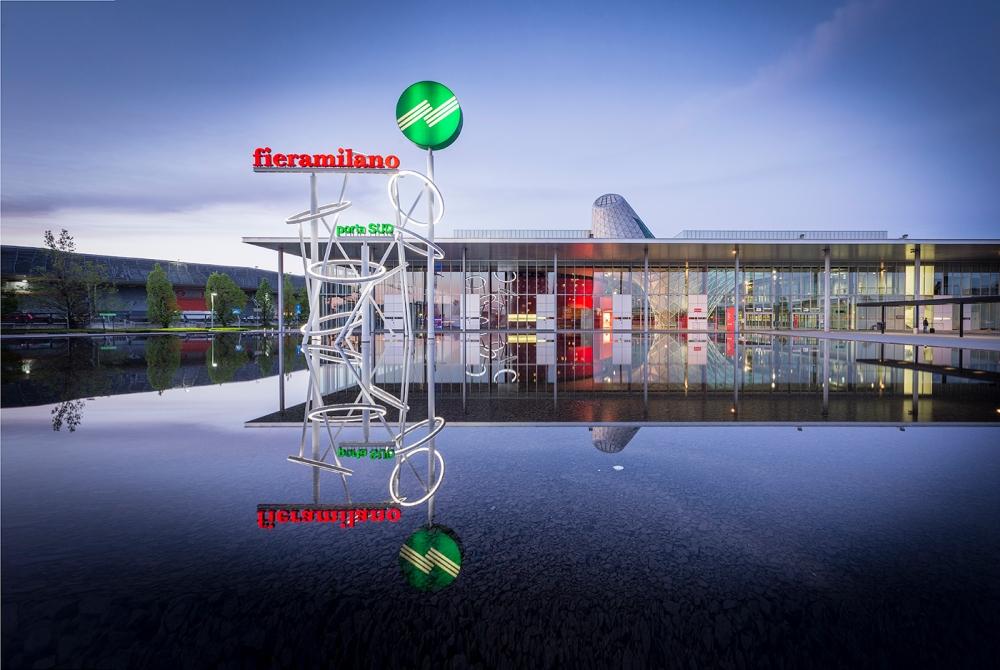 Il Salone del Mobile di Milano, nella nuova sede della Fiera di Milano a Rho, è una grande vetrina per il Design Italiano... al crepuscolo l'insegna si riflette insieme al cielo nel grande specchio d'acqua antistante la porta ovest.